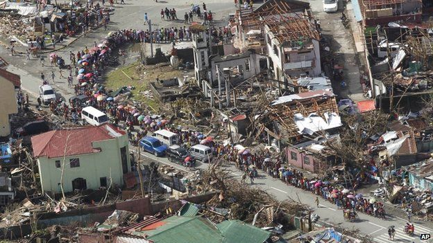 Hundreds of residents form a line for relief goods amid the destruction left from Typhoon Haiyan in the coastal town of Tanawan, central Philippines, 13 November, 2013
