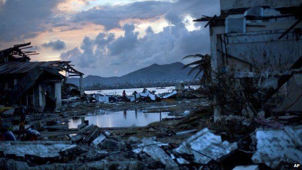 Typhoon Haiyan survivors walk through the ruins of Tacloban, central Philippines, 13 November