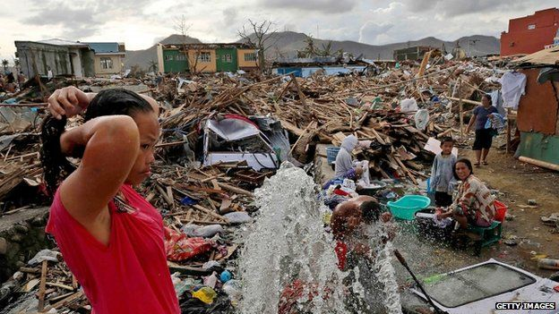A woman washes in the ruins of Tacloban, 13 November