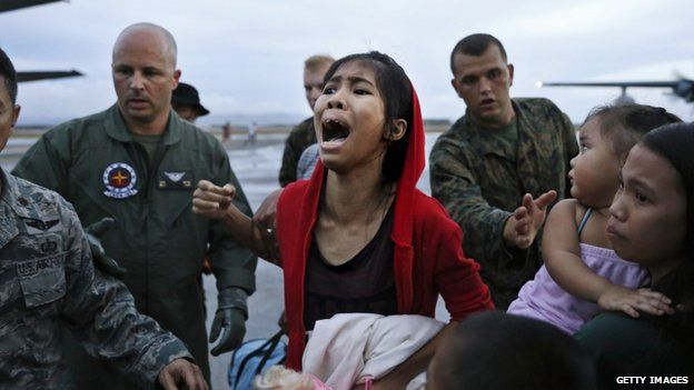 An evacuee cries for a relative while boarding a US military evacuation flight at the airport in Tacloban, 12 November