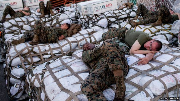US military personnel sleep on aid shipments at Tacloban Airport on 15 November 2013 in Leyte, Philippines