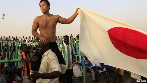 Japanese diplomat Yasuhiro Murotatsu holds up a Japanese flag after being defeated by Sudanese wrestler - 25 October 2013