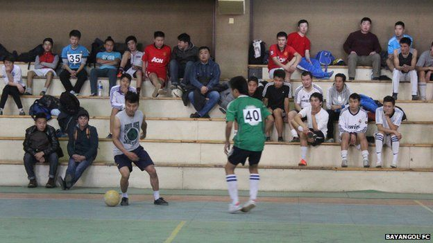 Two men playing football in a gym, with others watching
