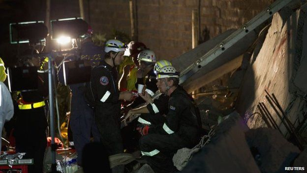 Emergency workers are seen during their search for survivors after a building collapsed in Tongaat