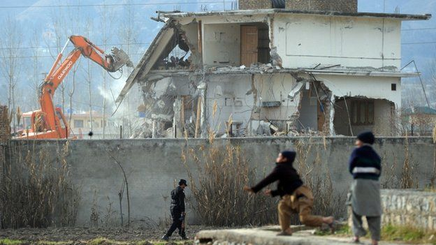 In this photograph taken on February 26, 2012, young Pakistani children play near demolition works on the compound where Al-Qaeda chief Osama bin Laden was slain in the northwestern town of Abbottabad