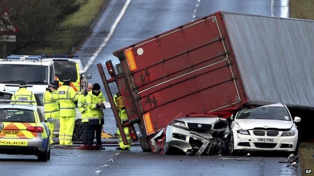 Emergency workers attend the scene of a fatal truck accident as a lorry sits on top of two cars near Bathgate, Scotland