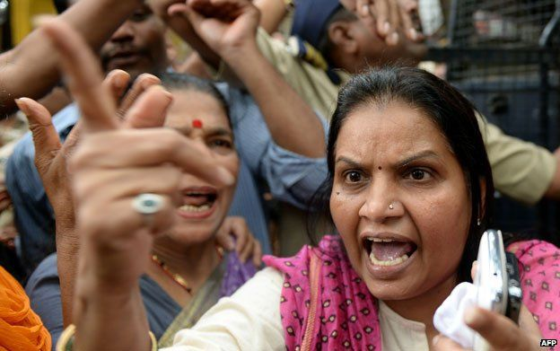 Activist argues with police officials outside the court after a suspect in the gang-rape of a female photographer was produced, in Mumbai