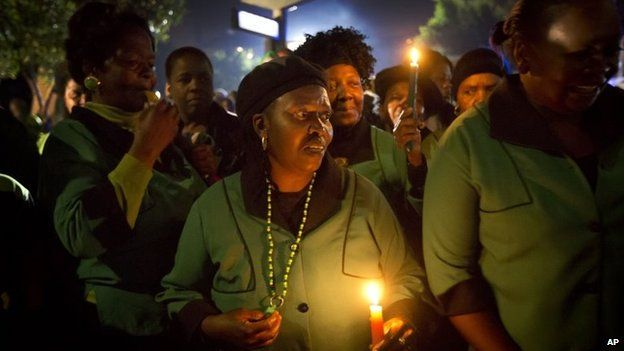 Members of the African National Congress (ANC) Womens League hold candles and sings songs outside Mr Mandela's old house in Soweto
