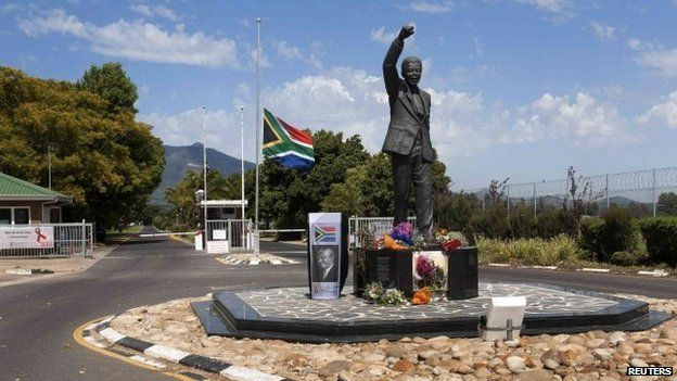 Wreaths of flowers and personal messages are left at the Mandela statue at the entrance of the Groot Drakenstein Prison, formerly Victor Verster Prison