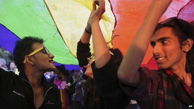 Gay rights activists display a rainbow-colored banner as they march in Delhi