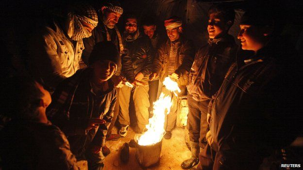 Syrian refugees gather around a fire in a Syrian refugee camp in the Lebanese border town of Arsal (13 December 2013)