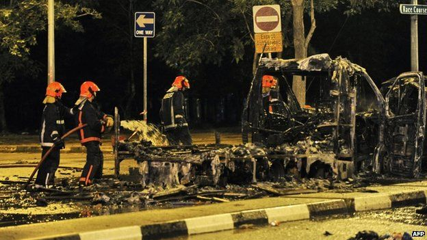 File photo: Firemen douse an ambulance charred in the riot in Little India, Singapore, 9 December 2013