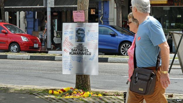 A couple walk past a tribute board set up for Indian national Sakthivel Kumaravelu in Little India, Singapore, 11 December 2013