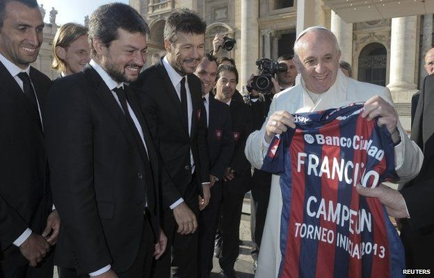 Pope Francis holds a jersey of Argentine soccer team San Lorenzo, given to him as a gift from members of the team, during the Wednesday general audience in St Peter's Square at the Vatican on 18 December, 2013