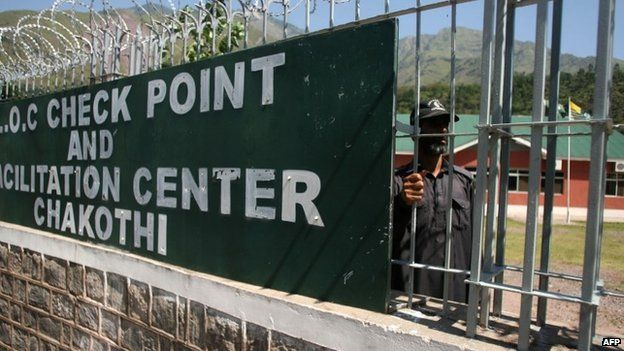 A Kashmiri security guard looks out of the truck check point at the Line of Control (LoC) A
