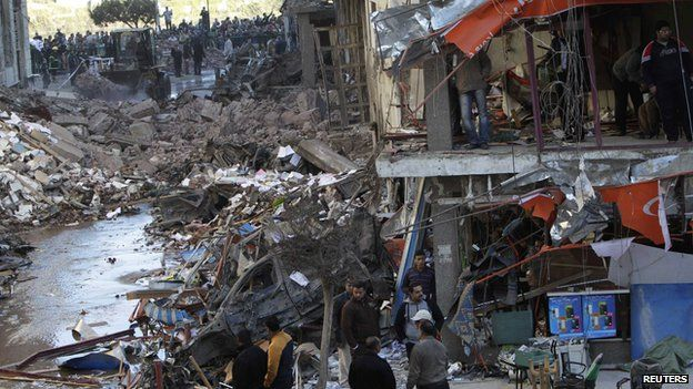 People look at the damage after an explosion near a security building in Mansoura