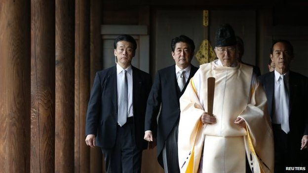 Shinzo Abe (2nd L) is led by a Shinto priest as he visits Yasukuni shrine in Tokyo December 26