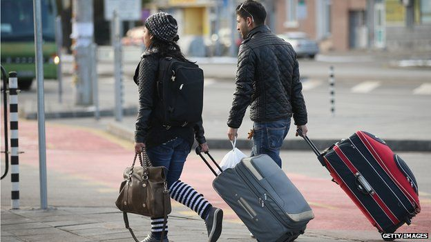 A young Roma couple walk with suitcases outside the main bus station on December 7, 2013 in Sofia, Bulgaria.