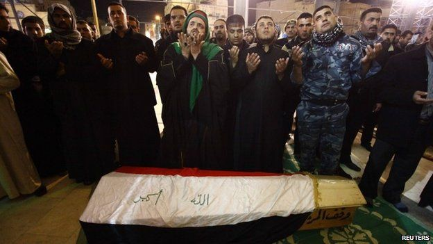 Mourners in the Shia holy city of Najaf pray near the coffin of a soldier killed in Anbar (2 January 2014)
