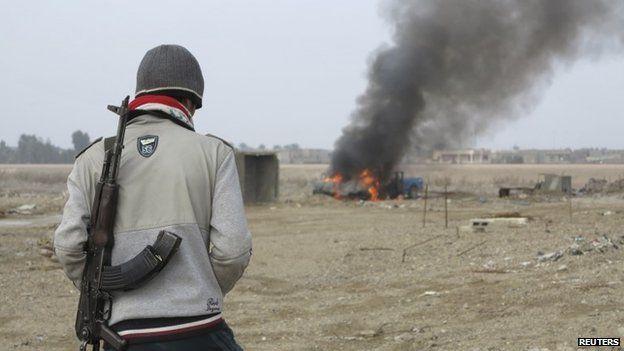 Iraqi militant looks at burning police vehicle in Ramadi (2 January 2014)