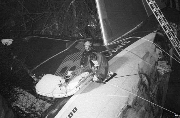 Rescuers sitting on top of the plane take a break