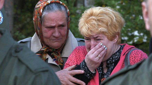 women crying at burial service