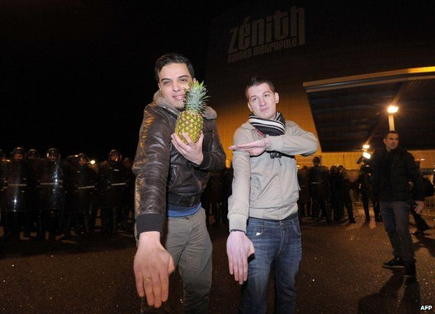 One man holds a pineapple while he and another makes quenelle salutes outside the Zenith concert hall in Nantes, 9 January