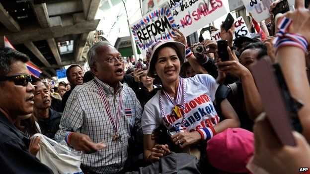 Thai protest leader Suthep Thaugsuban poses for a picture with a supporter as anti-government protesters march through downtown Bangkok on 15 January 2014