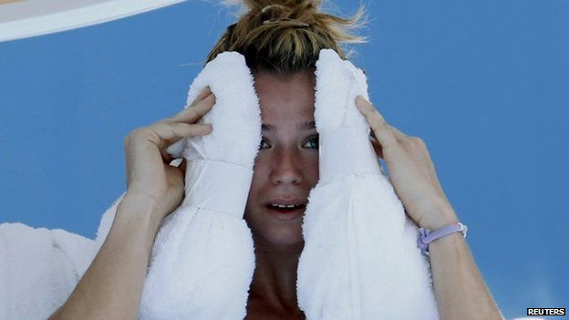 Camila Giorgi of Italy holds an ice towel to her face during her women's singles match against Alize Cornet of France at the Australian Open 2014 tennis tournament in Melbourne, 16 January 2014