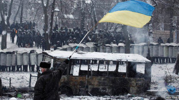 Man waves Ukrainian flag in front of riot police in Kiev on 22 January 2014