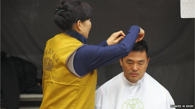 A volunteer cuts a man's hair at a Tzu Chi event on 18 January 2014