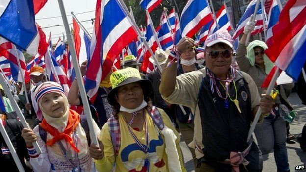 Thai anti-government protesters wave national flags as they parade during a rally in Bangkok on 24 January 2014