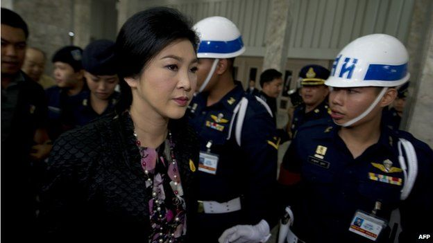 Thai Prime Minister Yingluck Shinawatra (C) leaves the Royal Thai Air Force building in Bangkok on 23 January 2014