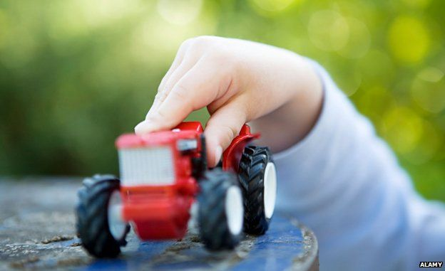 Child's and holding toy tractor