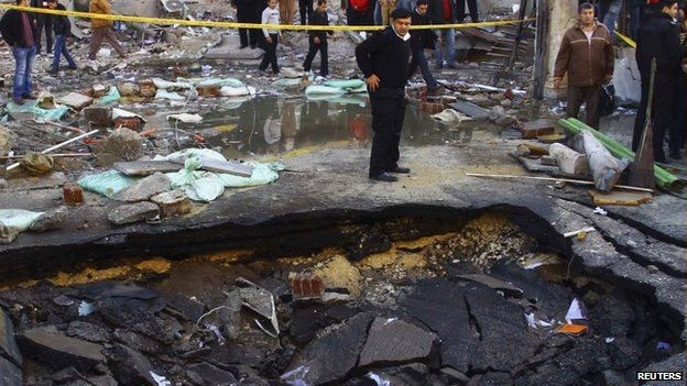 A police officer inspects a crater made after a bomb attack