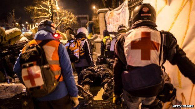 Medics carry a protester on a stretcher in Kiev (25 January 2014)