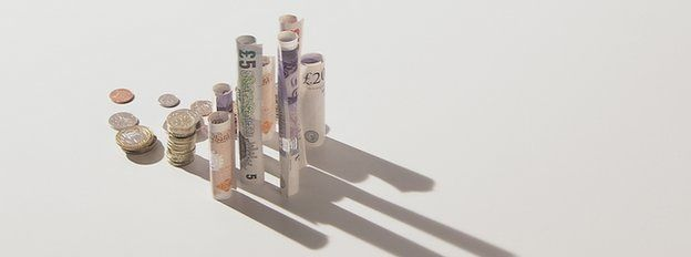 Notes rolled up and piles of coins arranges to look like a city skyline