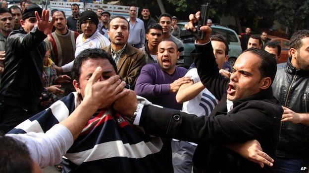 A plainclothes security officer, holding a gun, detains a supporter of ousted Islamist President Mohammed Morsi in the Cairo neighbourhood of Nasr City, Egypt, on Saturday