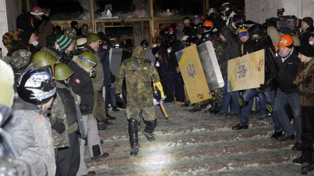 "Protesters create a corridor at a building""s entrance presumably for police to leave after an attack in central Kiev, Ukraine, 25 January"