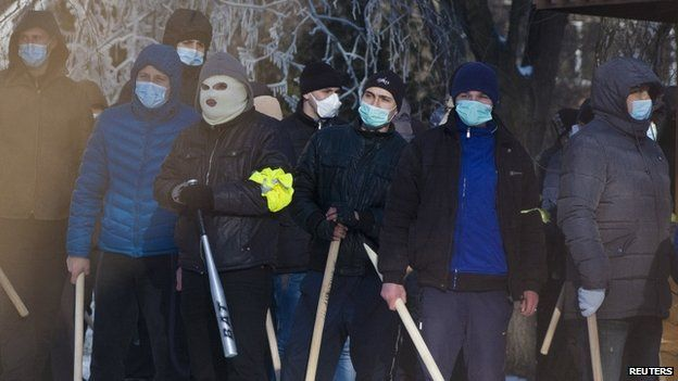 Masked men with bats watch a rally of anti-government protesters near the regional administration headquarters in the central Ukrainian city of Dnipropetrovsk on Sunday