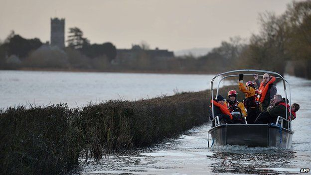 Residents are transported by boat over flood water at the cut-off village of Muchelney in Somerset, southwestern England, on January 27, 2014