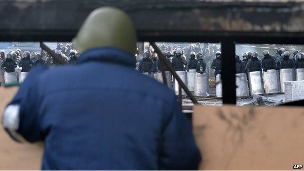 An anti-government protester looks at riot police at a road block in central Kiev on January 27