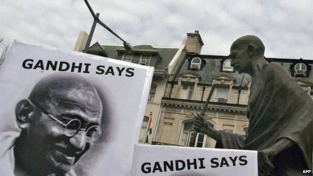 Peace activists hold signs with pictures of the late Indian leader Mohandas Karamchand Gandhi under his statue in front of the Indian Embassy in Washington.