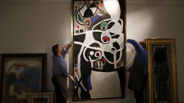 """In this 19 December file photo, auction house workers adjust Joan Miro""""s 1968 oil painting """"Women and Birds"""" in a room with other works by Miro, at Christie's auction house in central London."""