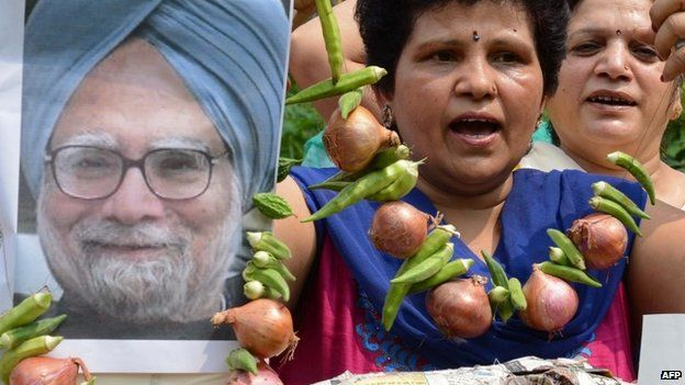 """Women""""s Welfare Organisation activists are pictured with an effigy of Indian Prime Minister Manmohan Singh, seen garlanded with vegetables including onions, during a demonstration in Amritsar on August 22, 2013."""