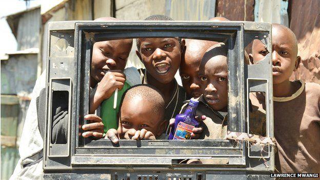 Children peeking through a broken TV set, copyright Lawrence Mwangi