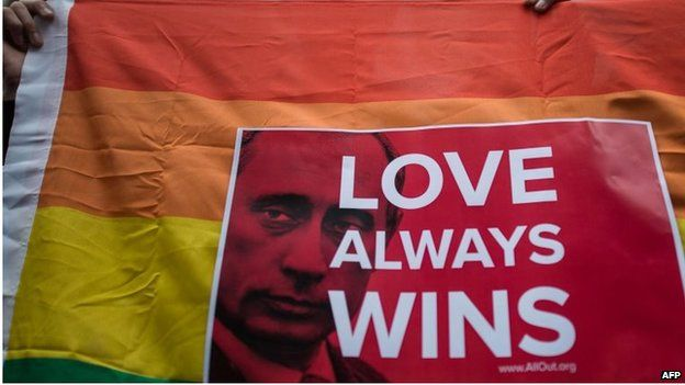 An activist holds a flag displaying a placard with a slogan over the face of Russian President Vladimir Putin during a demonstration against Russia's anti-gay legislation, in Hong Kong on 7 February