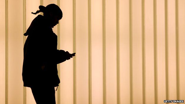 Woman uses smartphone by World Trade Center, New York