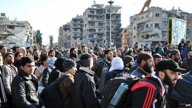Civilians wait to be evacuated by United Nations staff from the besieged district of the central Syrian city of Homs on 9 February 2014