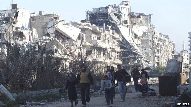 Civilians carry their belongings as they walk towards a meeting point to be evacuated from a besieged area of Homs on 9 February 2014